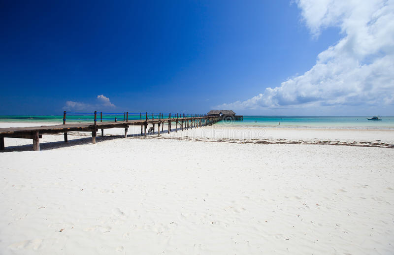 Tropical beach. Wooden jetty on white sand tropical beach on Zanzibar island royalty free stock image