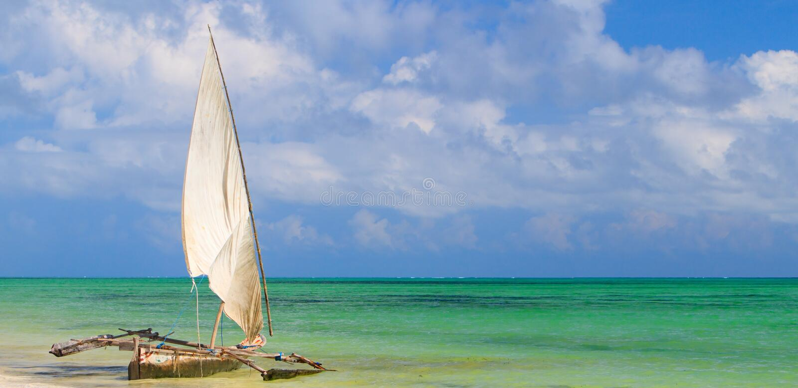 Tropical beach. Panoramic photo of white sand tropical beach and traditional Zanzibar boat stock photography