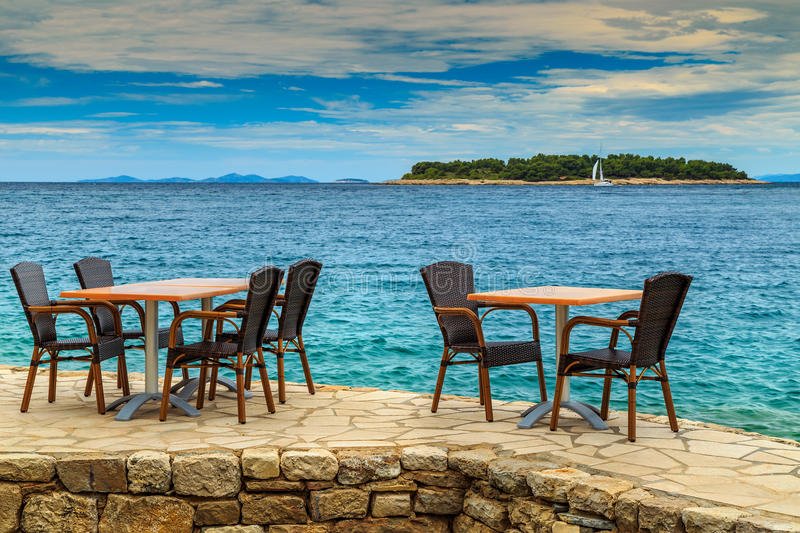 Tropical beach bar with table and wooden chairs stock photography