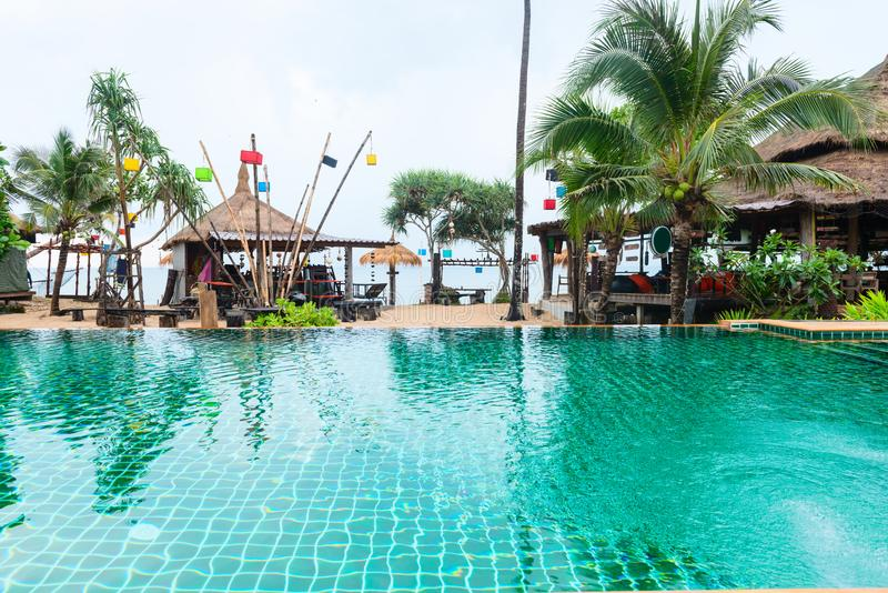 Tropical beach bars and restaurant with big clear swimming pool. Green palms and blue sea on background royalty free stock photos
