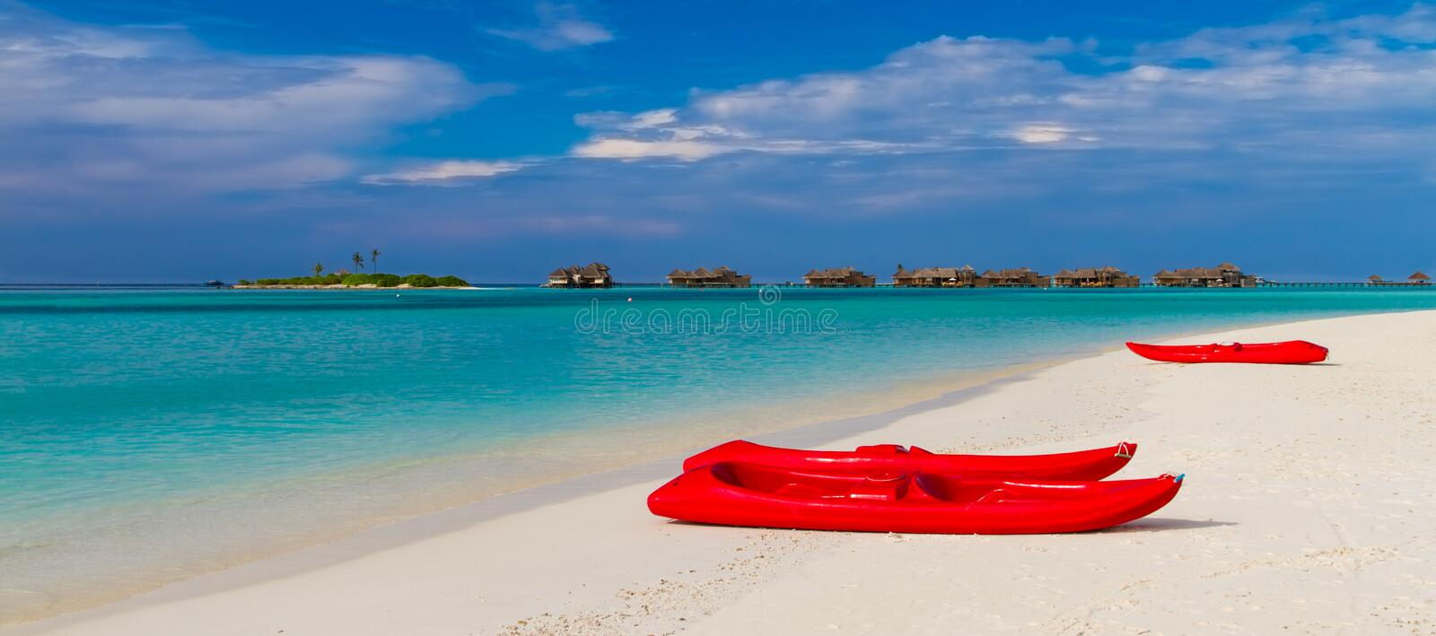 Tropical beach and blue lagoon. White sandy beach and blue lagoon with red kayaks royalty free stock images