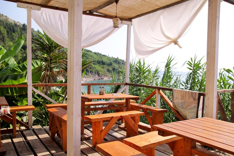 Tropical beach cafe bar at coastline by sea with outdoor view. Terrace balcony, relax place for eating and drinks of seaside. stock photos