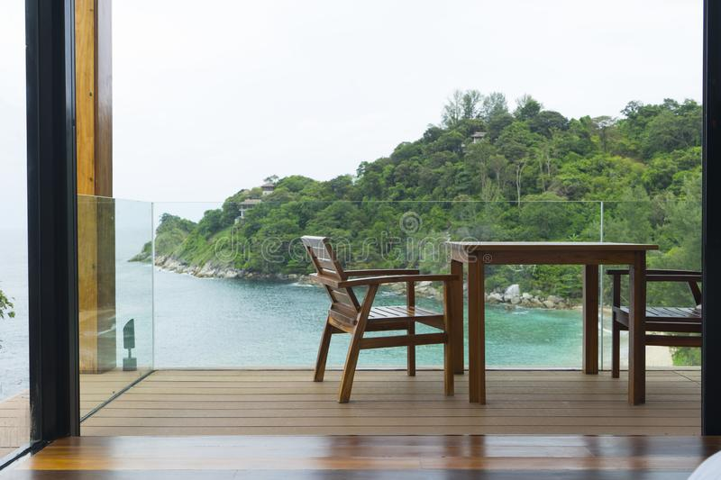Tropical beach with chairs for relaxation on wooden terrace. stock photo