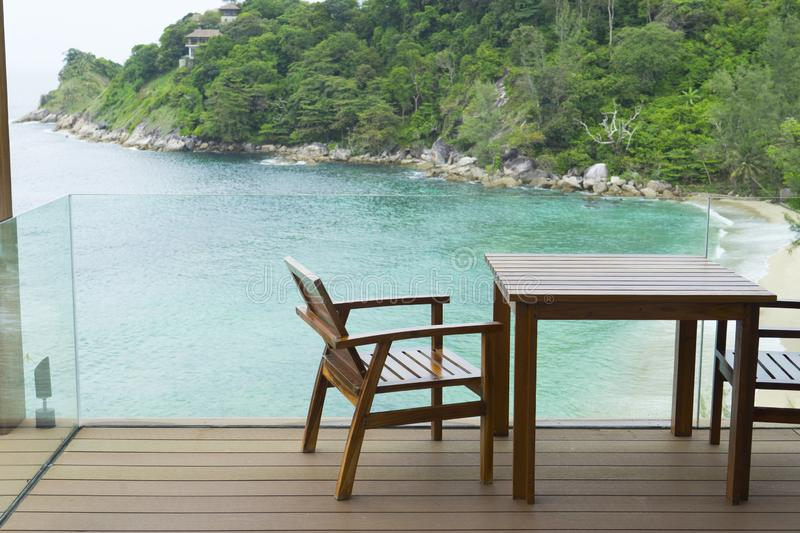 Tropical beach with chairs for relaxation on wooden terrace. royalty free stock image