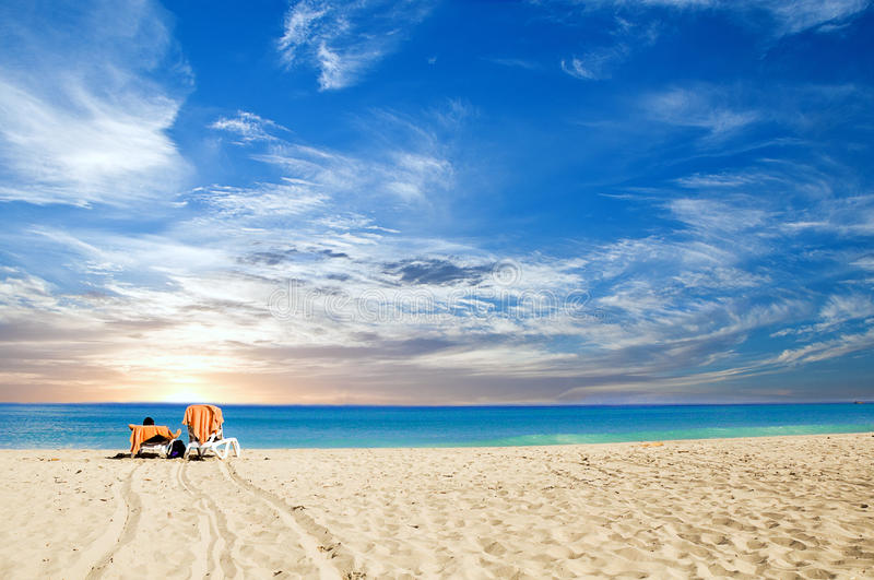 Tropical beach dawning. A view of a person enjoying in a tropical beach dawning stock photos