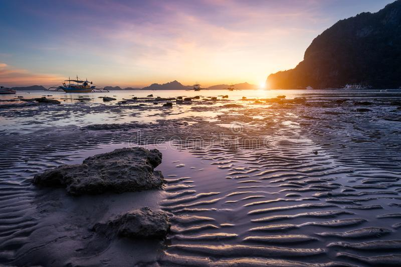 Tropical beach in ebb time low tide on sunset. Mudflats and sun reflections at the golden hour. mountain chain isles at stock image