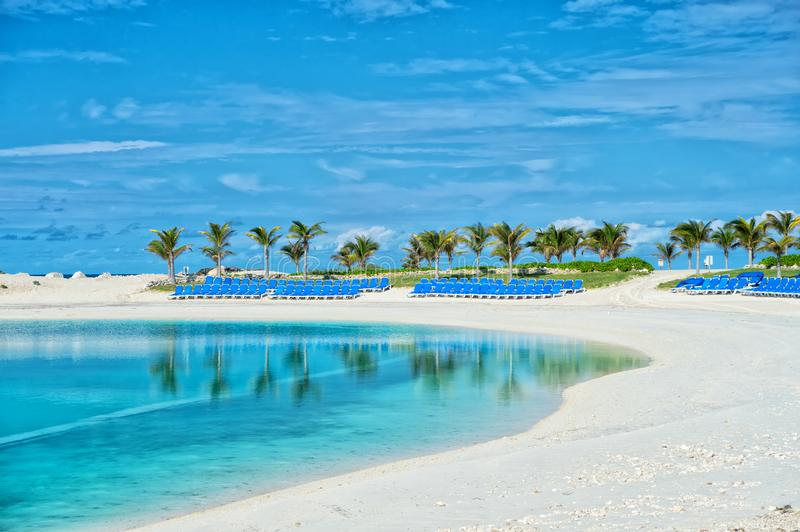 Tropical beach in Great Stirrup Cay, Bahamas. Sea shore, white sand, palm trees on blue sky. Summer vacation, recreation, resort. Paradise, peace, romance stock photography