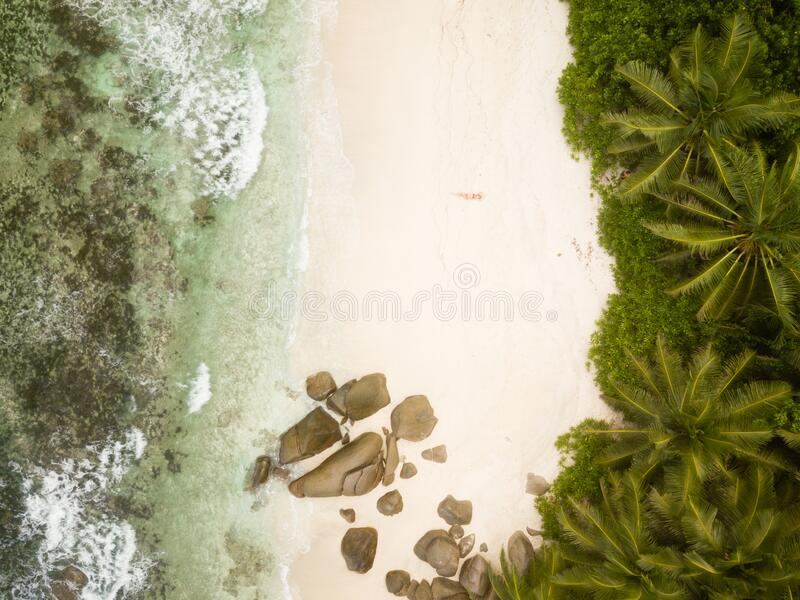 Tropical beach with palm trees, sandy beach and typical granite rocks and a woman in red bikini from high above, birds eye view, d stock image