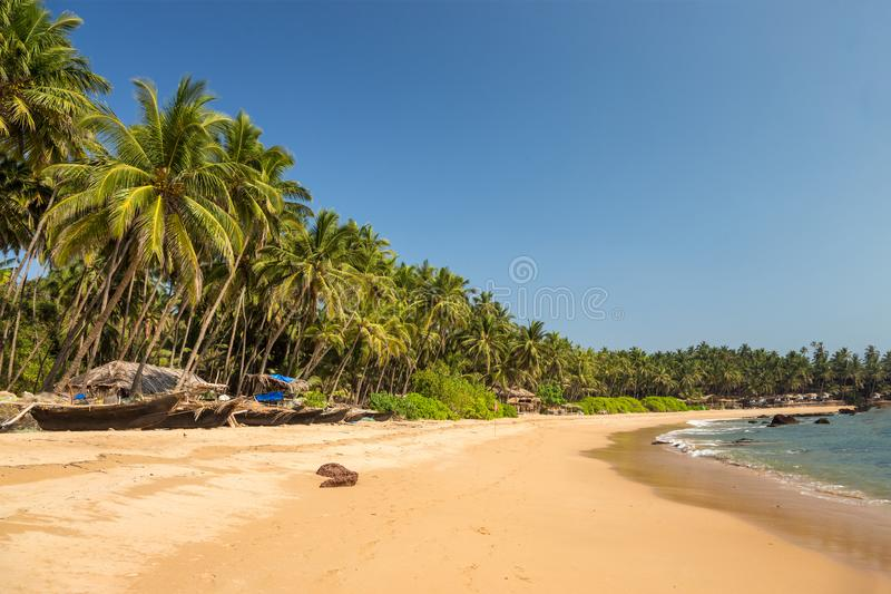 Tropical beach with a row of fishing boats royalty free stock photography