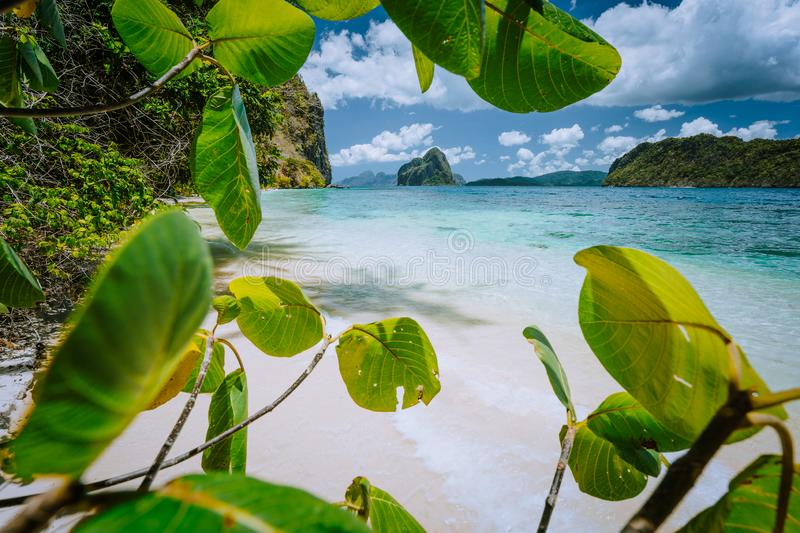 Tropical beach scenery with rocky islands and impressive clouds, framed with lush vegetation. Exploring Philippines. Palawan royalty free stock photos