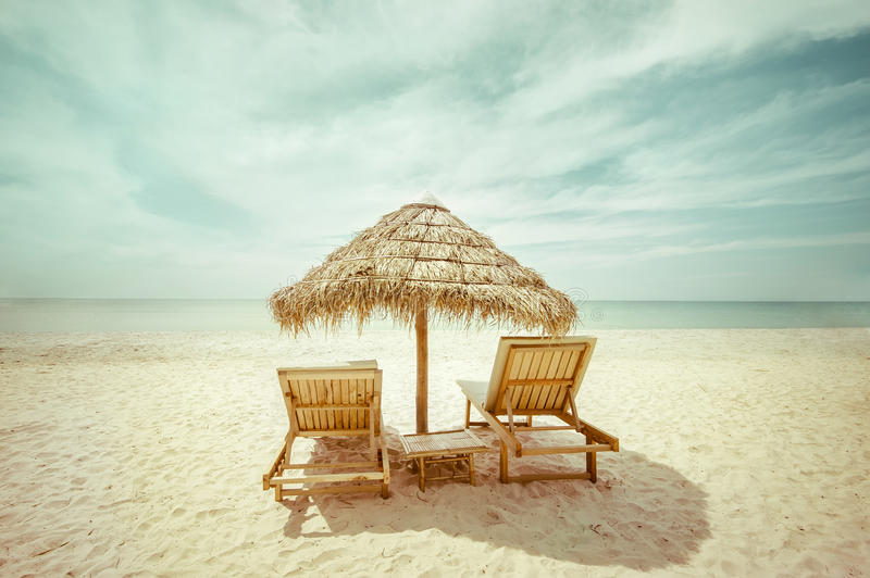 Tropical beach with thatch umbrella and chairs for relaxation. Amazing tropical beach landscape with thatch umbrella and chairs for relaxation on sand. Travel royalty free stock photo
