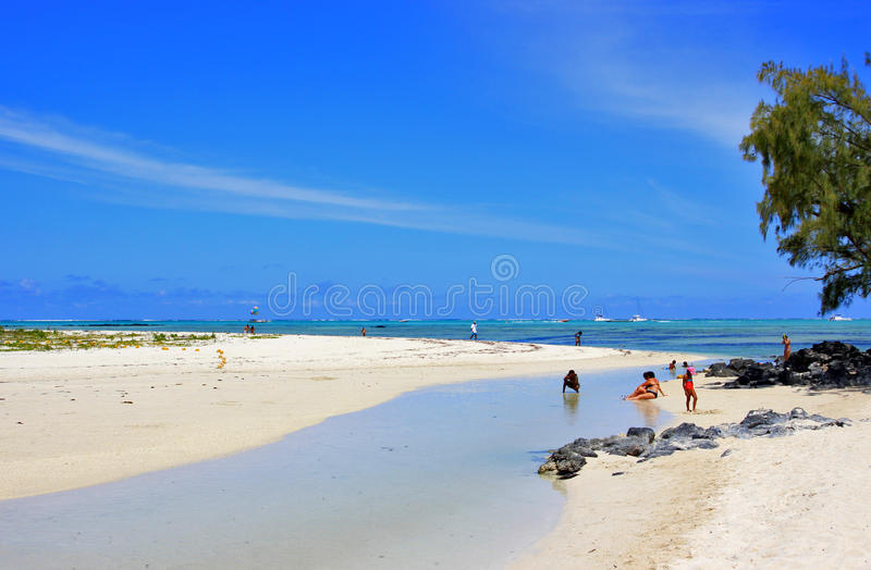 Tropical beach and tourists. Tropical beach with white sands and tourists in Mauritius royalty free stock image