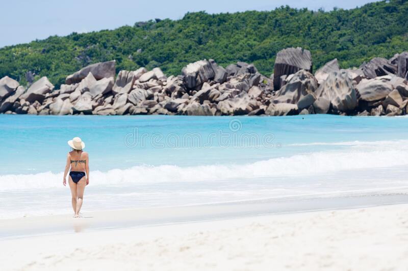 Tropical beach, turquoise blue water surrounded with huge rocks, and a walking woman in sun hat. royalty free stock photography