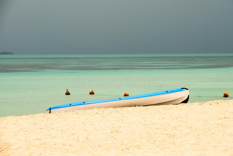 Small water craft at beaches edge, incoming storm stock image