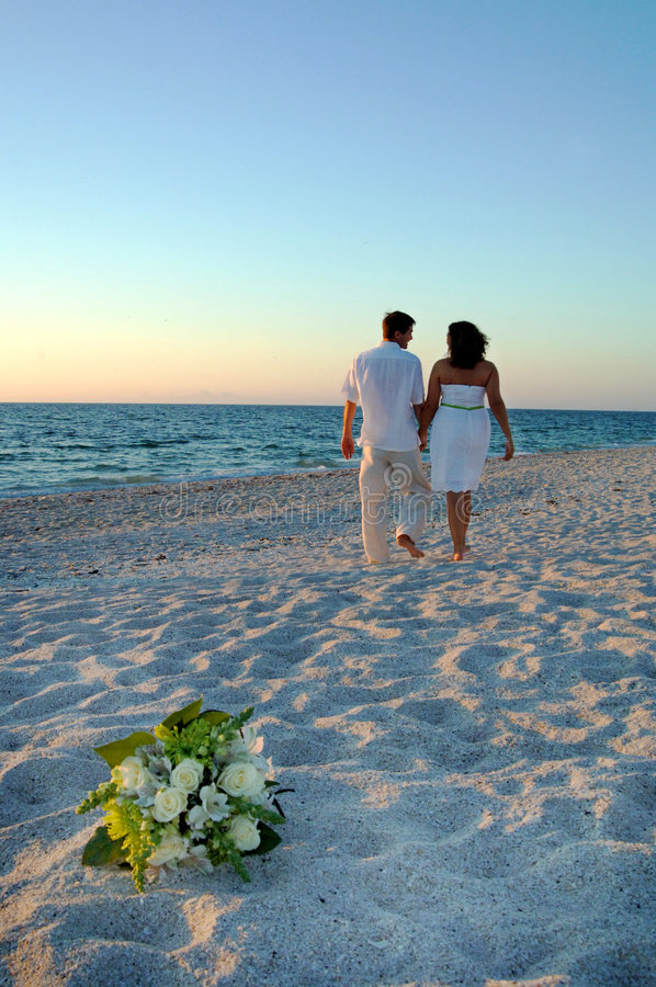 Tropical Beach wedding. A bride and groom walking on the beach after wedding at sunset stock photos