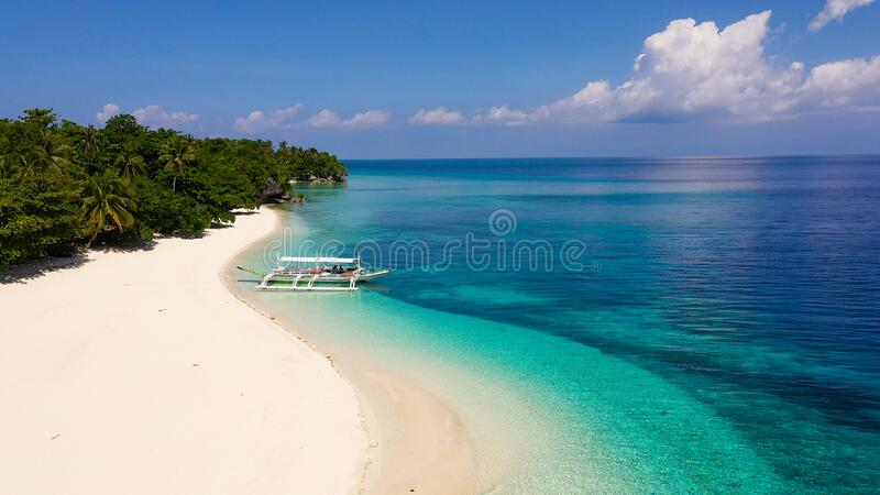 Tropical beach of white sand, top view. Tourist boat off the coast. Tranquil beach scene. Tropical beach of white sand, top view. Tourist boat off the coast stock photography