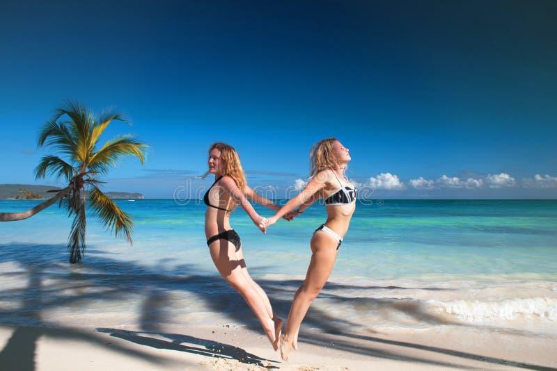 Tropical beach, women having fun, jump love heart symbol stock photos