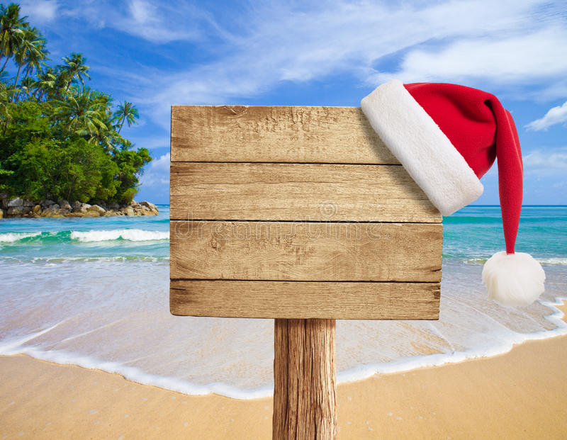 Tropical beach wooden signboard with Christmas hat. Hanging royalty free stock images