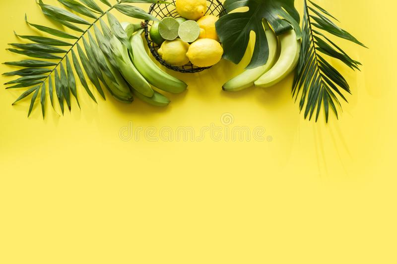 Tropical border of fruits, banana, lime, leaves palms on punchy yellow background. Space for text. Detox tour stock photo