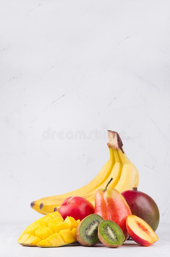 Tropical bright fruits - mango, banana, kiwi, pear, peach, nectarine on soft white wood board with copy space, vertical. Tropical bright fruits - mango, banana stock photography