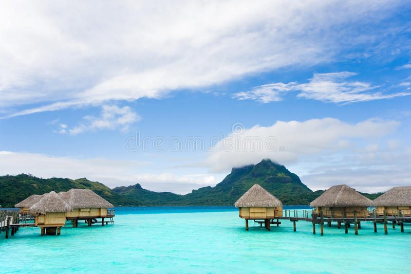 Tropical bungalows. Tropical overwater bungalows in bora bora tahiti above turquoise waters royalty free stock images