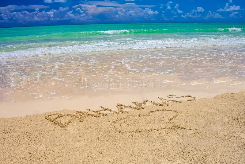 Tropical Caribbean beach in Bahamas with bright blue sky, turquoise water and writing on the sand stock photos