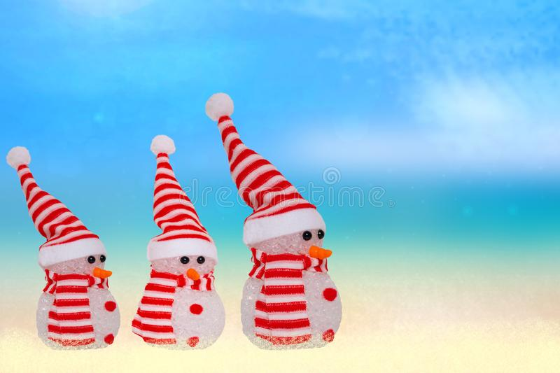 Tropical christmas background. A snowmen family with red white striped hat and scarf at astract tropical sandy beach with blue sky stock images