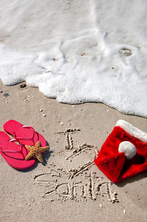 Tropical Christmas at the beach. Tropical Christmas at the beach, with flip flops, sunglasses, a starfish and santa hat, and `I heart Santa` written in the sand stock photography