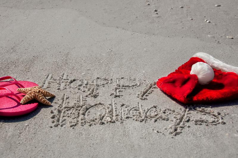 Tropical Christmas at the beach, with happy holidays written in. The sand, flip flops, a starfish and santa hat stock photos