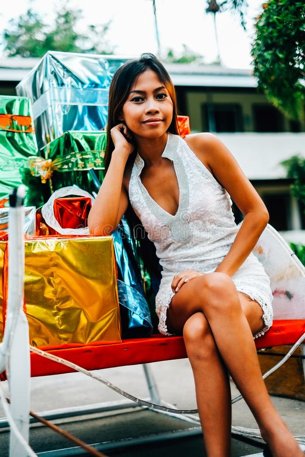 Tropical Christmas concept. Young woman in Santa Claus sledge with shiny colorful gifts.  stock images