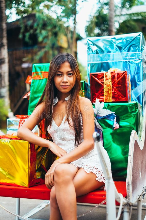 Tropical Christmas concept. Young woman in Santa Claus sledge with shiny colorful gifts.  royalty free stock images