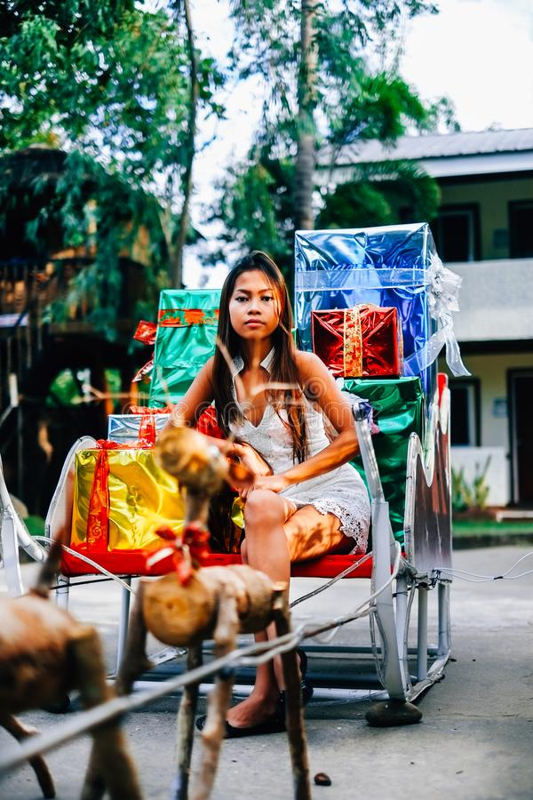 Tropical Christmas concept. Young woman in Santa Claus sledge with shiny colorful gifts.  stock photos