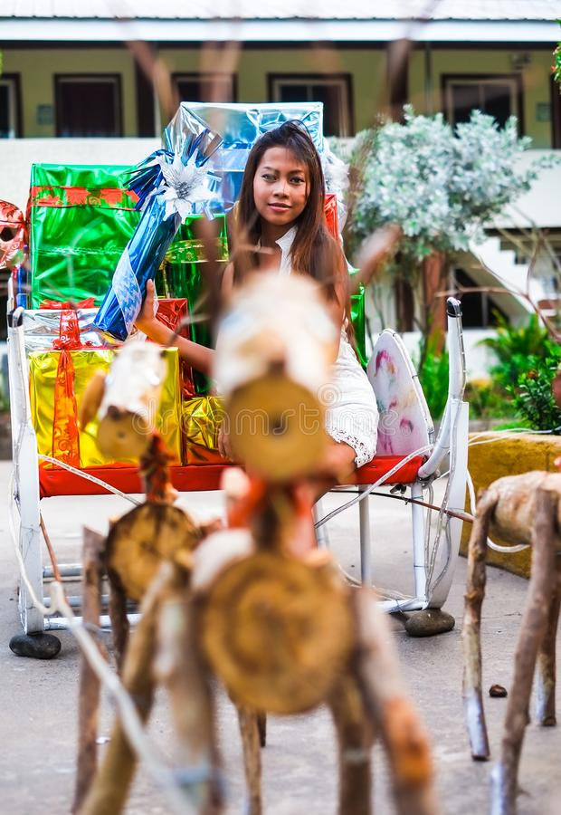 Tropical Christmas concept. Young woman in Santa Claus sledge with shiny colorful gifts.  royalty free stock photo
