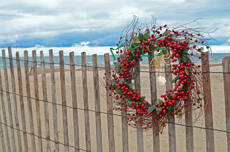 Red berry Christmas wreath with tropical starfish. Sand dollar and starfish decorating a berry Christmas wreath on beach fence stock photography