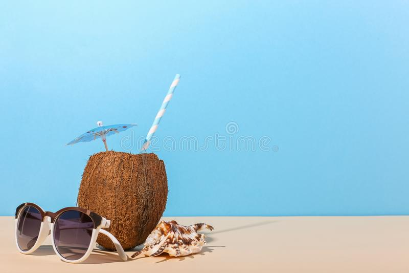 Tropical cocktail in coconut with straw and an umbrella, on paper blue and yellow background. The concept of relaxation, summer royalty free stock photo