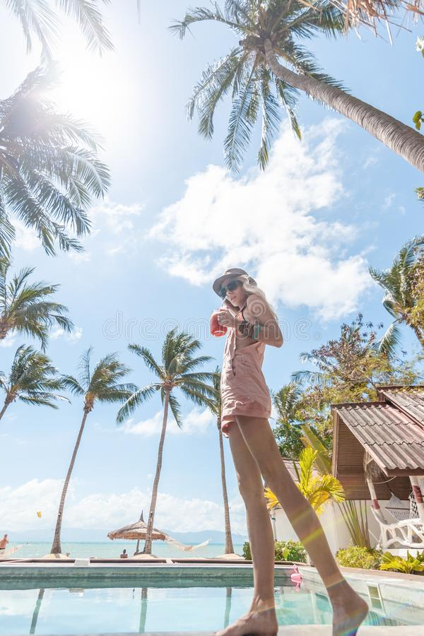 Tropical coconut summer landscape. Slim young woman on beautiful summer day. Summer vacation. royalty free stock photos