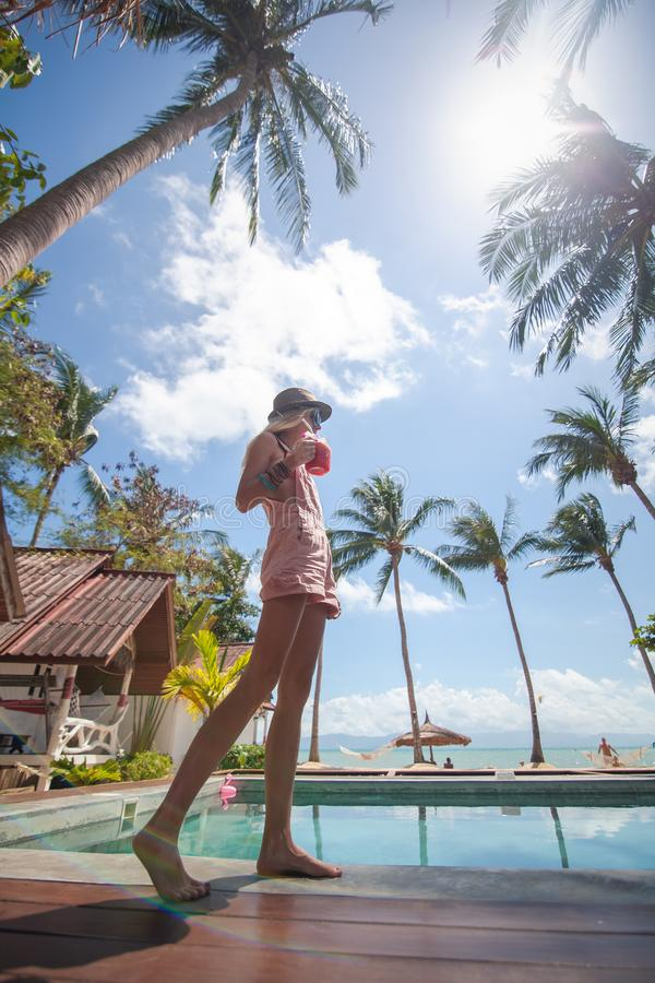 Tropical coconut summer landscape. Slim young woman on beautiful summer day. Summer vacation. royalty free stock photo
