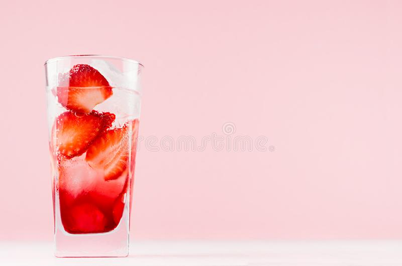 Tropical cool alcohol strawberry drink with sparkling soda, ice cubes on elegant pink color background and white wood board. Tropical cool alcohol strawberry stock photo