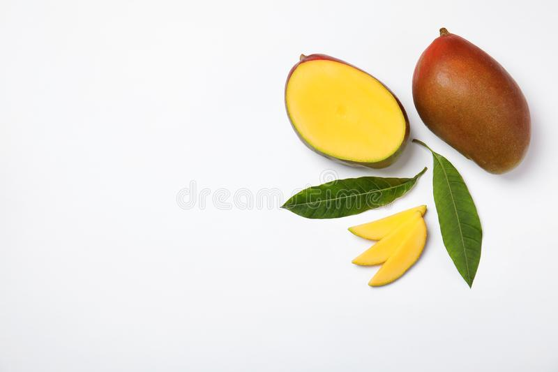 Tropical cut and whole mango with green leaves isolated on white, flat lay. Space for text stock image