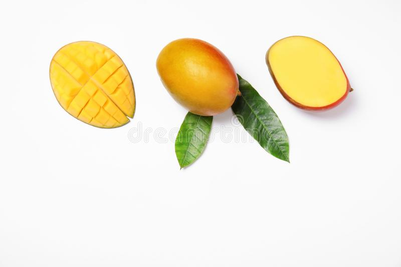 Tropical cut and whole mango with green leaves isolated. On white, flat lay. Space for text stock image