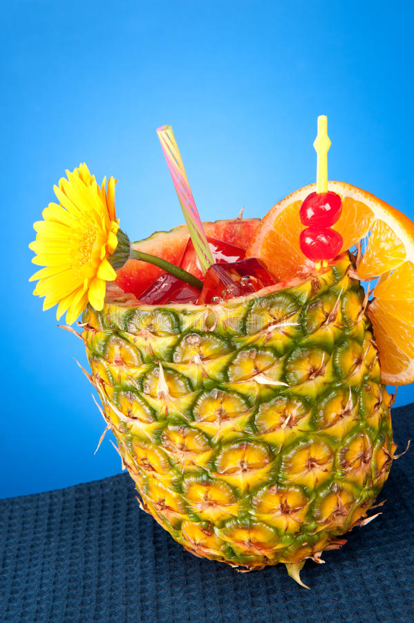 Tropical drink. A cold, refreshing tropical rum drink with a pineapple glass, strawberry, cherries and an orange slice shot against a blue gradient royalty free stock image