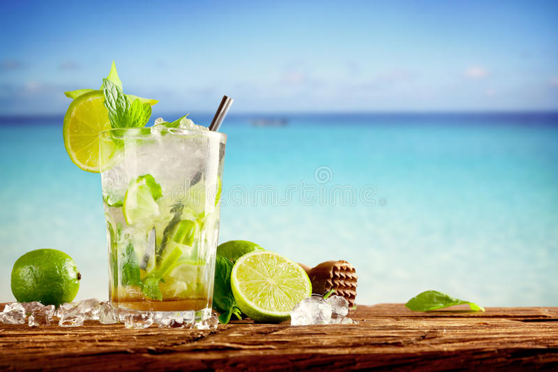 Tropical drink. Mojito drink on wood with blur beach on background royalty free stock photos