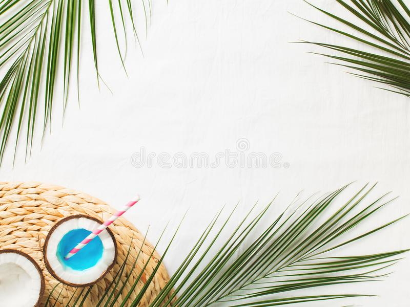 Tropical flat lay with palm leaves and blue cocktail in coconut. On white background royalty free stock images