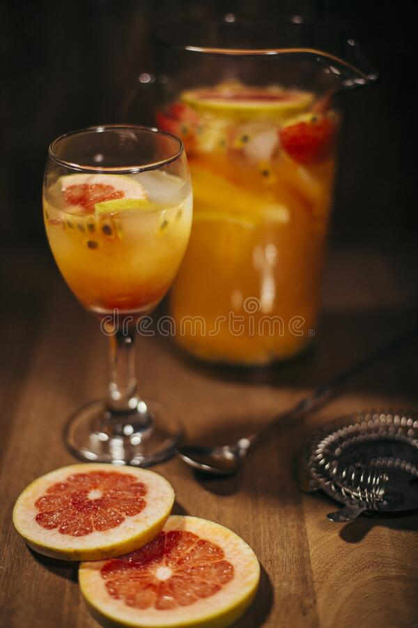 Iced Red Grapefruit and Passion fruit Vodka jar. Tropical flavored cocktail with grapefruit, passion fruit, vodka and ice on a wood surface. vintage mood royalty free stock image