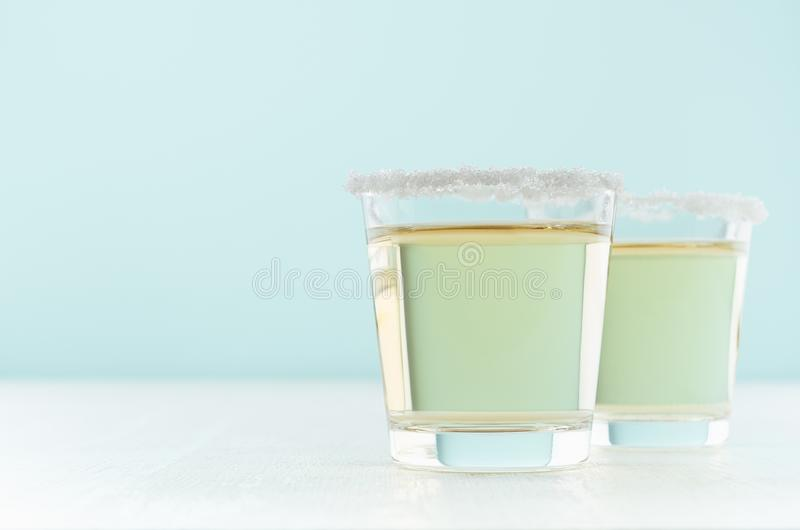 Tropical fresh alcohol yellow drink - golden tequila in two shot glasses with rim of salt in elegant pastel green color kitchen. royalty free stock photo