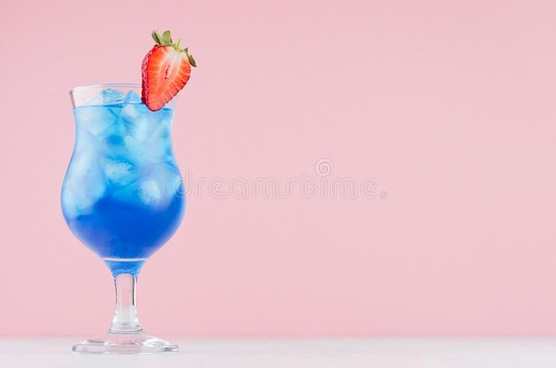 Tropical fresh blue drink with curacao, ice cubes, strawberry in exquisite misted wineglass on pastel pink wall, white table. stock image