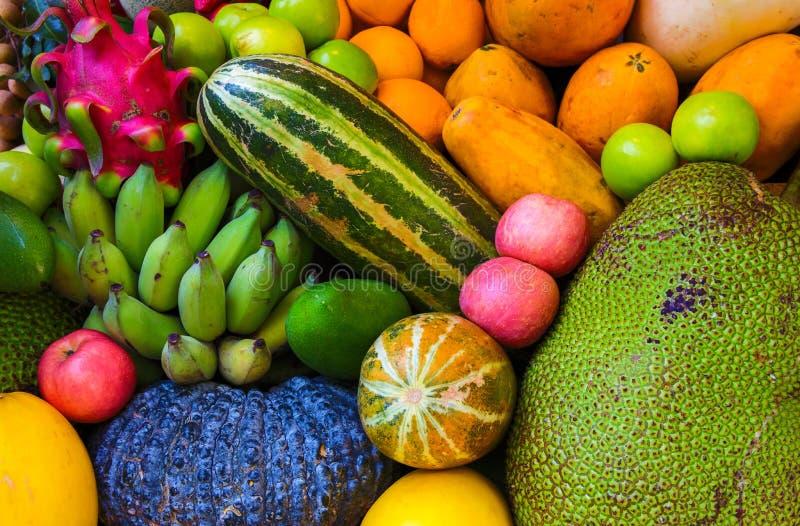Tropical fruit background. Raw and ripe exotic fruit closeup photo. Vegetarian wallpaper. Healthy food. Yellow papaya and mango. Green jackfruit and banana stock photography