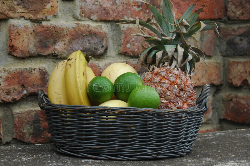 Tropical fruit basket. On a stone bench royalty free stock image