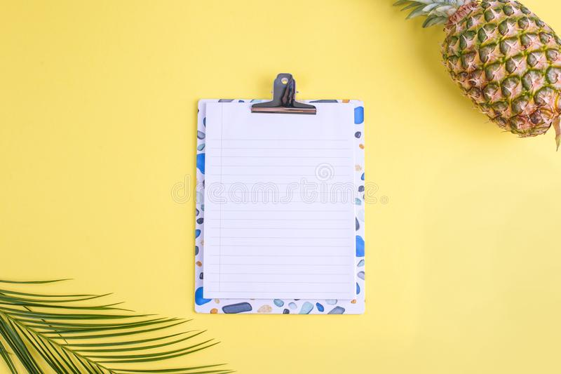 Tropical fruit, and a palm branch on a yellow background. Free space for text on a white board in the center. Copy space, flat lay royalty free stock photography