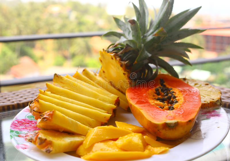 Tropical fruit pineapple, mango, corambola, papaya. On the plate served on palm tree for dietary light breakfast stock image